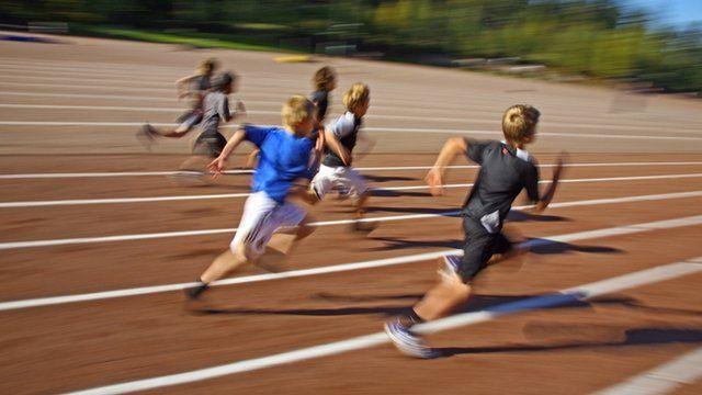 School children running on athletics track