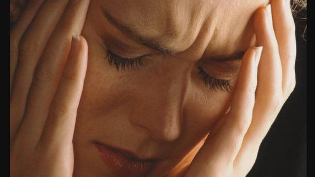 woman stressed with head in hands