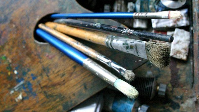 Paintbrushes, a palette and oil paints