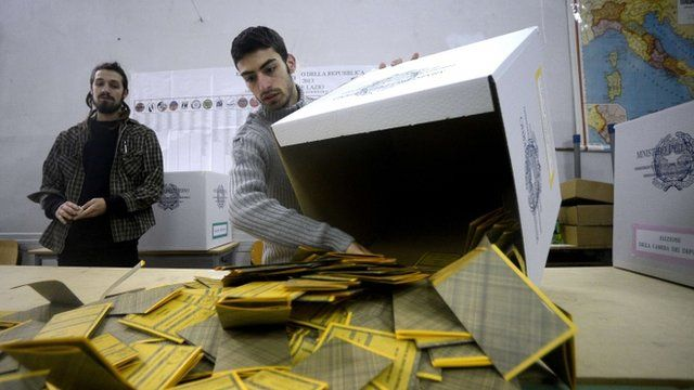 Workers open the ballots in a polling station