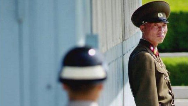 North South Korea border - A North Korean soldier, right, looks at his South Korean counterpart as they stand guard across the border line