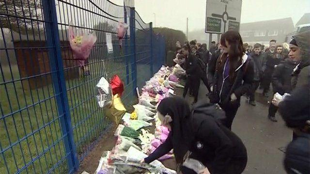Flowers being laid outside Leasowes High School in Halesowen