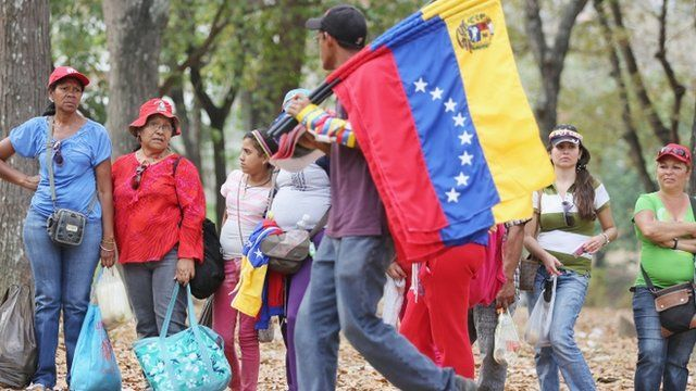 Man carrying Venezuelan flags