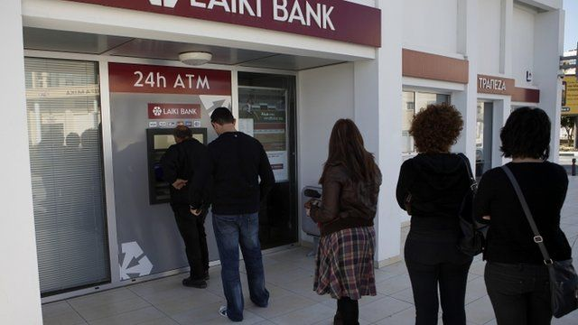 People queuing to use an ATM