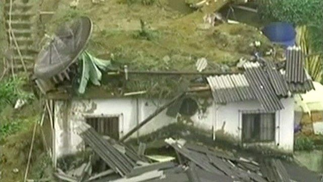 House missing its roof, covered in mud and debris from landslide