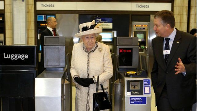 The Queen walks through a ticket barrier