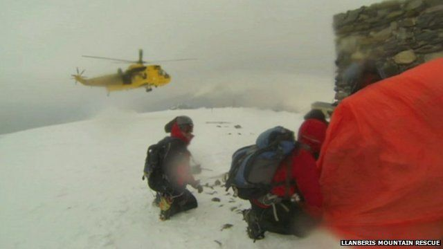 Mountain rescue helicopter landing near climbers in Snowdonia