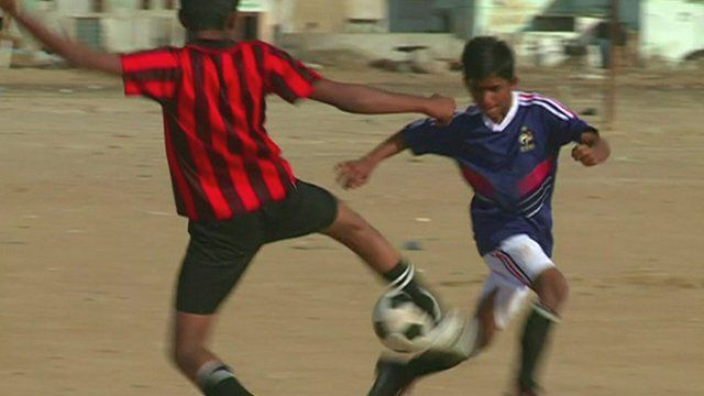 Two street children in Pakistan fight for possession of the ball