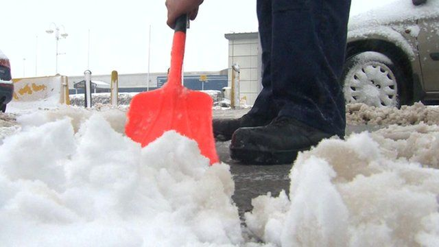 Man clearing snow with shovel