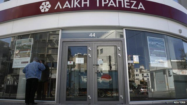Man peers into closed Cypriot bank