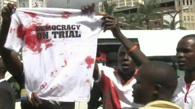 "Supporters of Raila Odinga holding up T-shirt saying ""democracy on trial"""