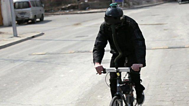 """Matt Hope wearing fighter pilot helmet while riding the """"breathing bike"""""""