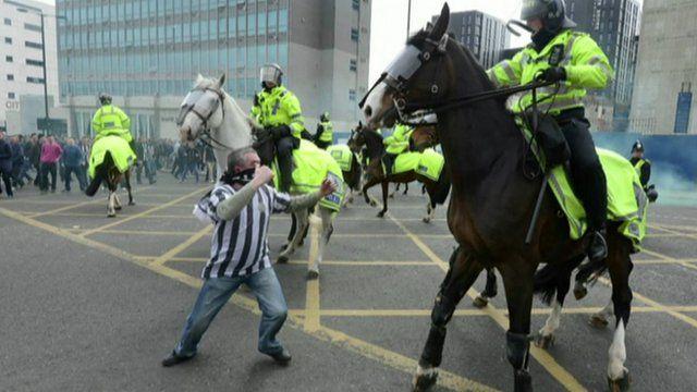 Football fan and policemen on horseback