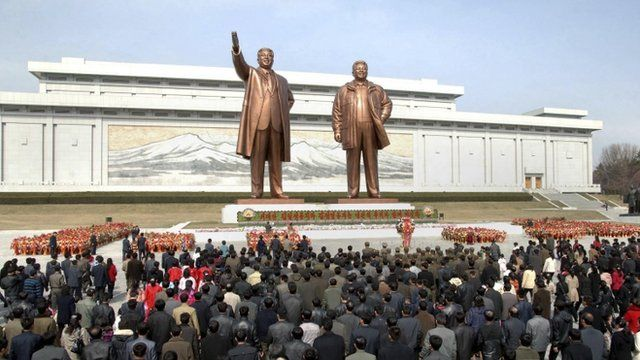 North Korean soldiers, workers and students place flowers before the statues of North Korean founder Kim Il-sung (left) and his son, late leader Kim Jong-il