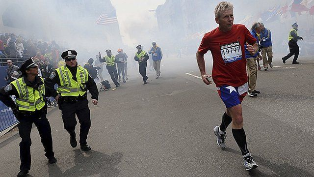A man runs from an explosion at the Boston marathon on 15 April 2013