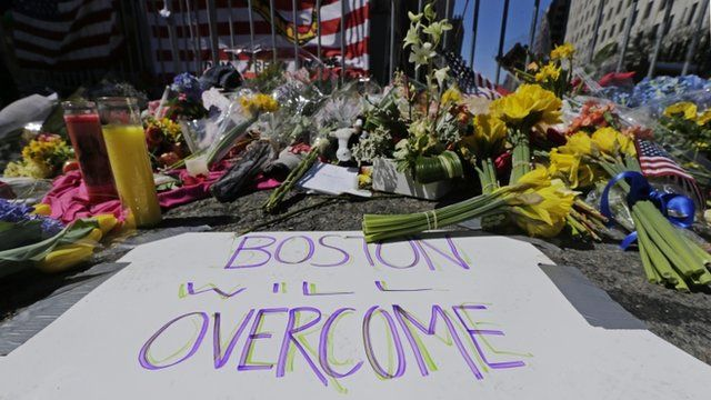 """Flowers and signs adorn a barrier at Boylston Street near the of finish line of Monday""""s Boston Marathon explosions"""