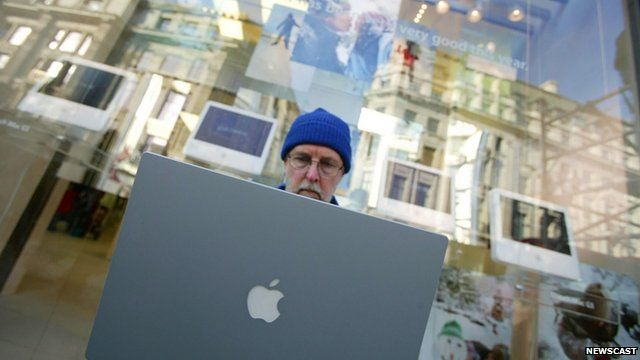 Customer logs onto a laptop while waiting for new Apple store in London to open
