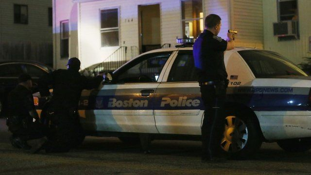 A police officer with gun drawn searches for a suspect on April 19,