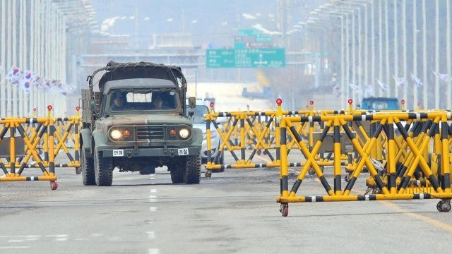 """A South Korean military vehicle drives past barricades on the road leading to North Korea""""s Kaesong industrial complex,"""