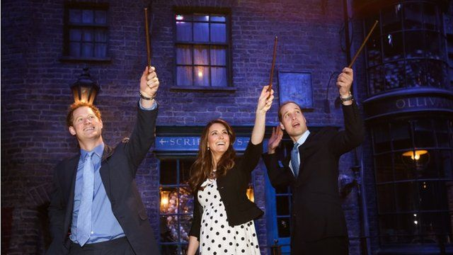 Prince Harry, Catherine, Duchess of Cambridge and Prince William, Duke of Cambridge raise their wands