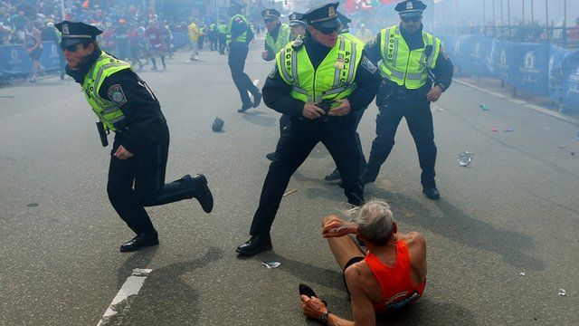 Police officers react to a second explosion at the finish line of the Boston Marathon