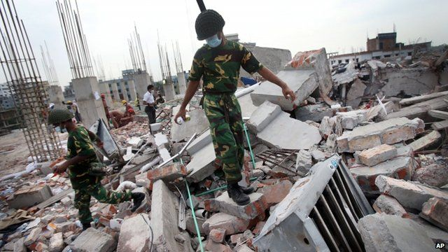 A soldier climbs on debris from the garment factory building that collapsed