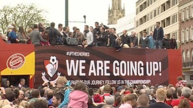 Bournemouth players and fans celebrate during an open-top bus parade in the town