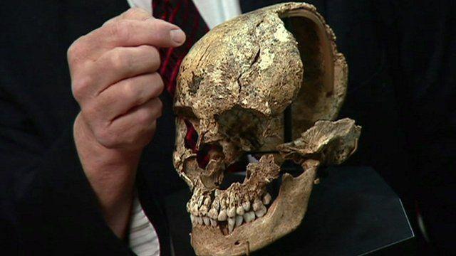 man points at skull