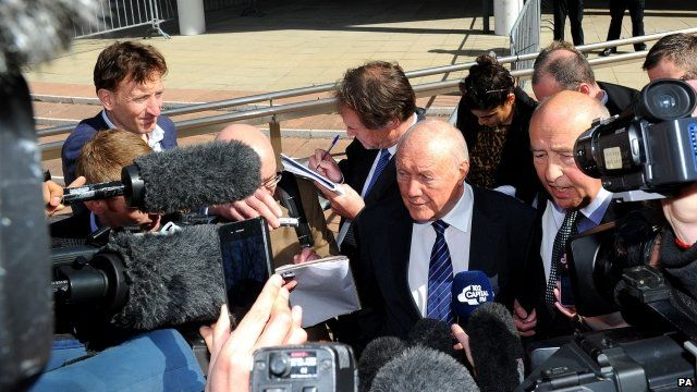 Stuart Hall (next to the man who is speaking) outside court