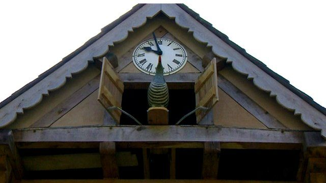 A wooden cuckoo coming out of a giant cuckoo clock