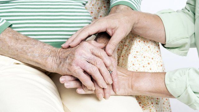Elderly person's hands with carer