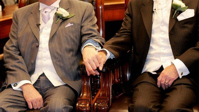 A gay couple hold hands