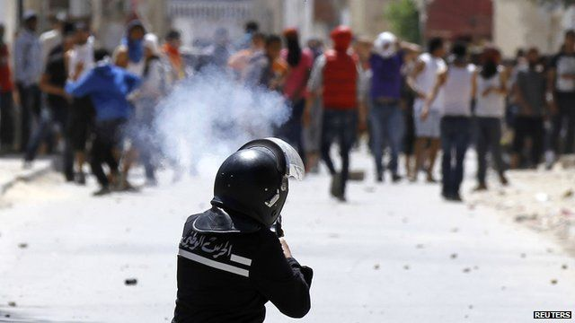 A riot police offers fires teargas in Tunisia