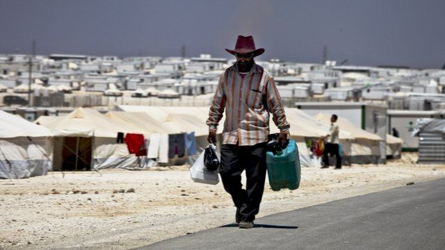 A Syrian refugee carries a jerrycan of water and food as he walks on the main street that connects the old section with tents to the new area with trailers, at the Zaatari refugee camp, near the Syrian border, in Mafraq, Jordan