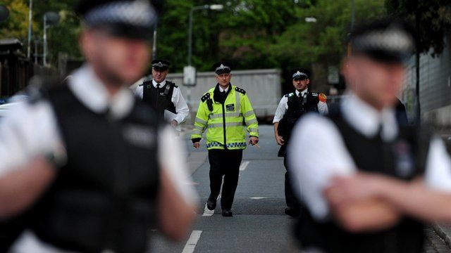 Police officers cordon off a road area in Woolwich, east London