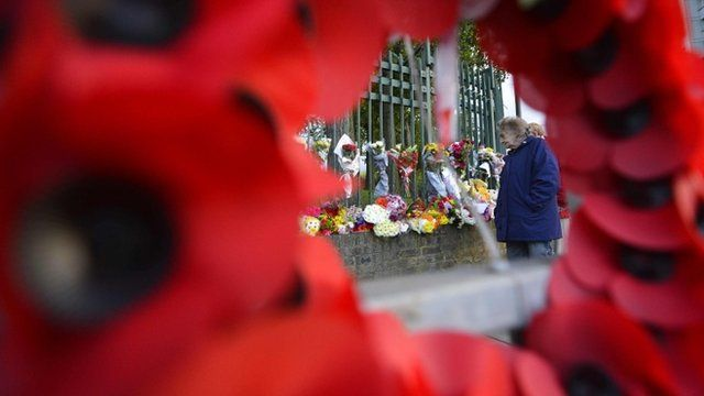 A woman views flowers and notes left in memory of victim Drummer Lee Rigby in Woolwich, south east London
