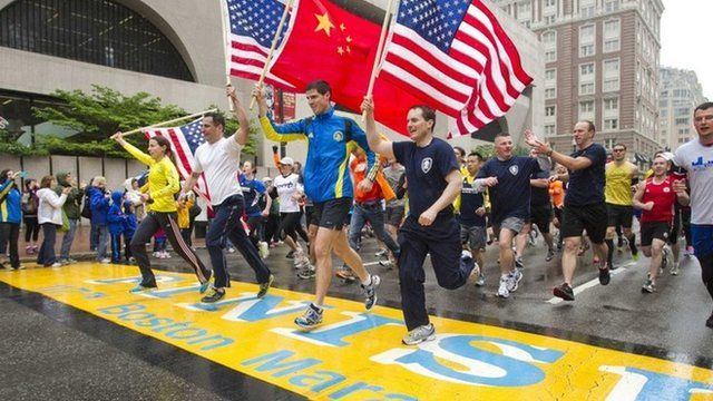 Runners holding three American flags and one Chinese cross the finish line of the Boston Marathon (25 May 2013)