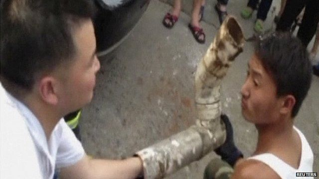 Chinese firefighters try to reach a trapped baby inside a sewage pipe