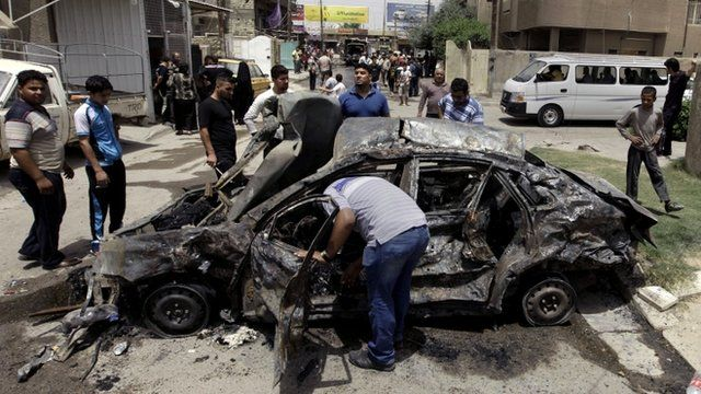 Civilians inspect the site of a parked car bomb attack near a popular restaurant in the Ur neighborhood in northern Baghdad