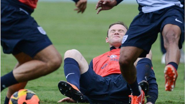 "England""s national football team player Wayne Rooney (C) falls during a training sesssion in Rio de Janeiro, Brazil, on May 31, 2013"