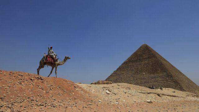 A man rides a camel past a pyramid at Giza