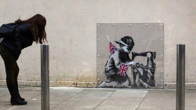 Woman looking at Banksy mural