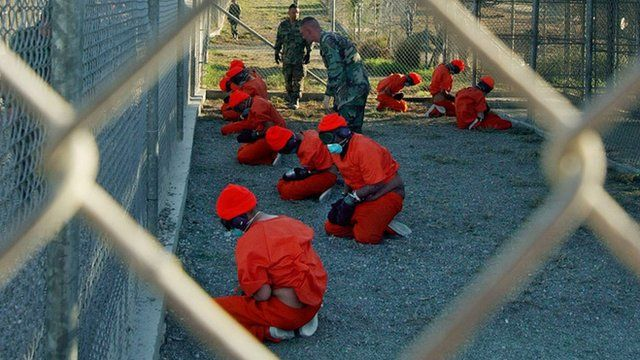 Taliban and al-Qaida detainees in orange jumpsuits sit in a holding area at Camp X-Ray at Naval Base Guantanamo Bay