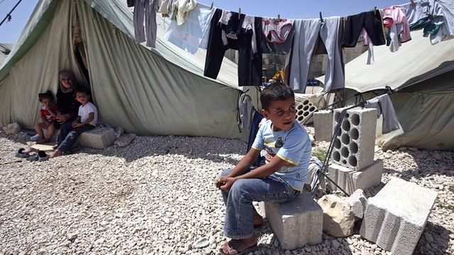 A Syrian boy sits outside his tent next to his family at a temporary refugee camp in the eastern Lebanese town of Marj