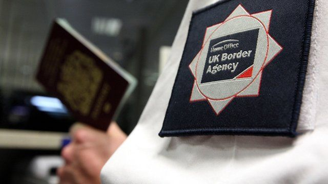 UK Border Agency official inspects a British passport