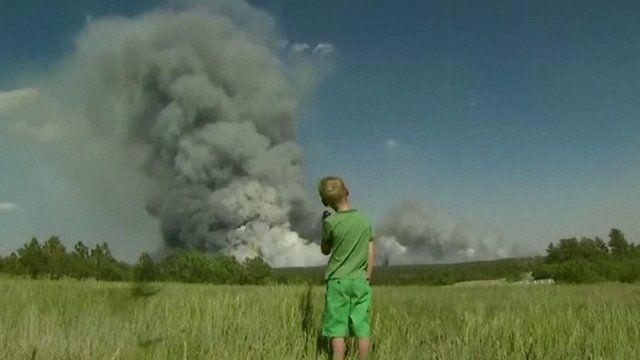 Boy watches plumes of smoke