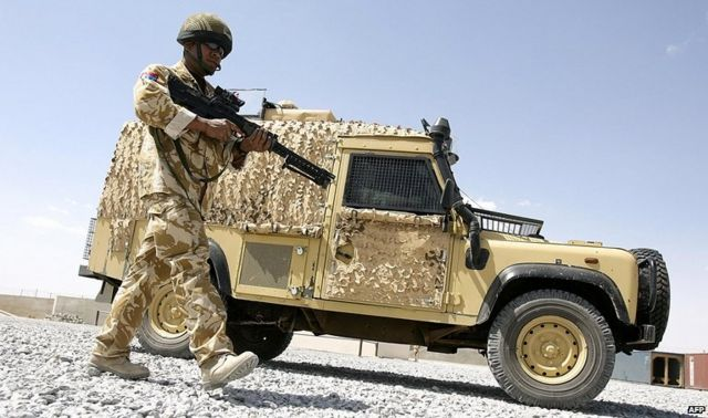 Soldier patrolling with Snatch Land Rover