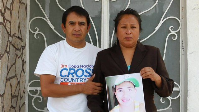 Mexican couple hold photo of their missing son