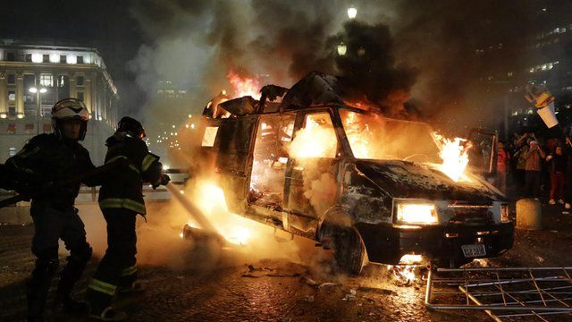 Firefighters and burning vehicle set on fire by protestors