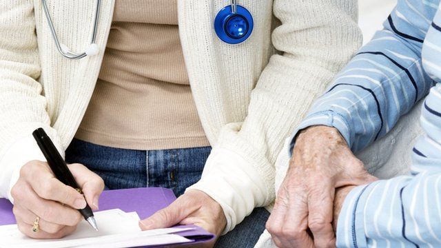 GP and elderly patient filling in a form